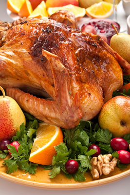 roast turkey with vegetables and fruit on a platter