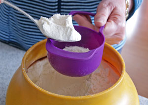 spooning flour into measuring cup